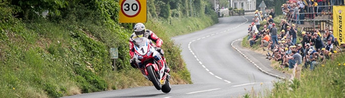 John McGuinness gets the front wheel up on his Honda CBR1000RR at the Isle of Man TT