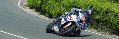 Ian Hutchinson gets knee down on his Tyco BMW S1000RR at the Isle of Man TT
