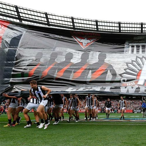 Collingwood players running through the banner at the ANZAC Day Clash