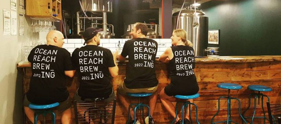 "alt=""Ocean Brewing staff siting on stools"""