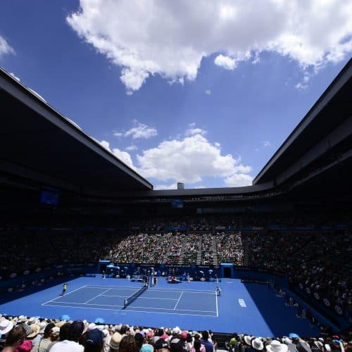 "alt=""Australian Open at Melbourne Park on a sunny day with a packed crowd"""