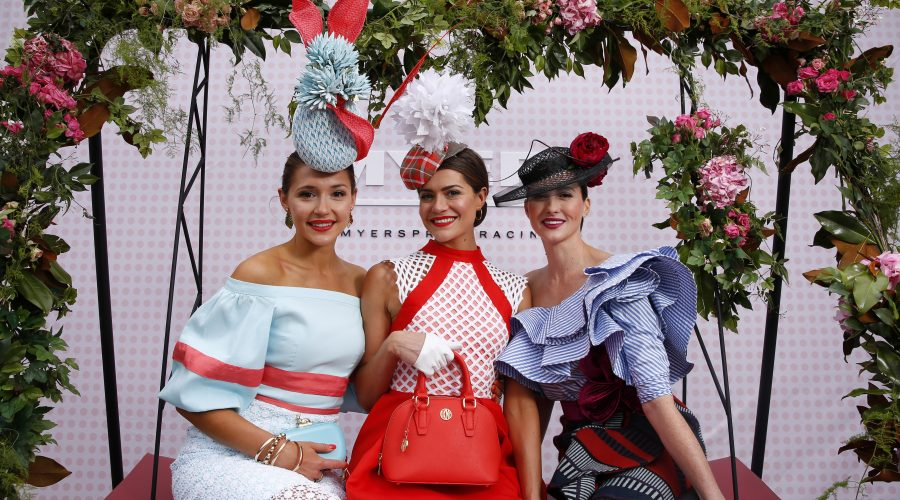 "alt=""Melbourne Cup Packages, Melbourne Cup 2017 Tickets, 2017 Melbourne Cup, formally dressed women posing on a swinging seat"""