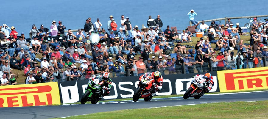 "alt=""Superbikes Championship, 3 Motorcycle riders racing with crowd full of people watching"""