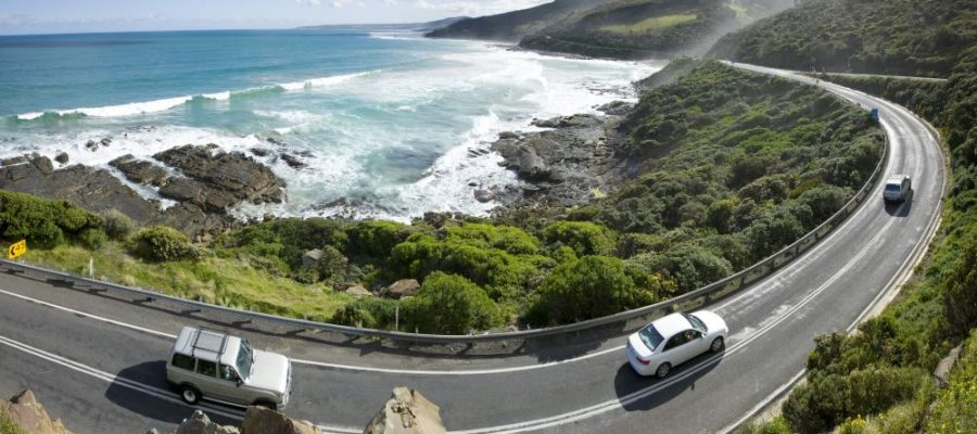 "alt=""Birds eye view of bending road with a gorgeous ocean view"""