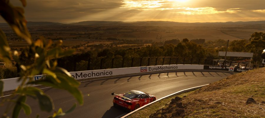 "alt=""supercar driving along while the sunset beams down on the road"""