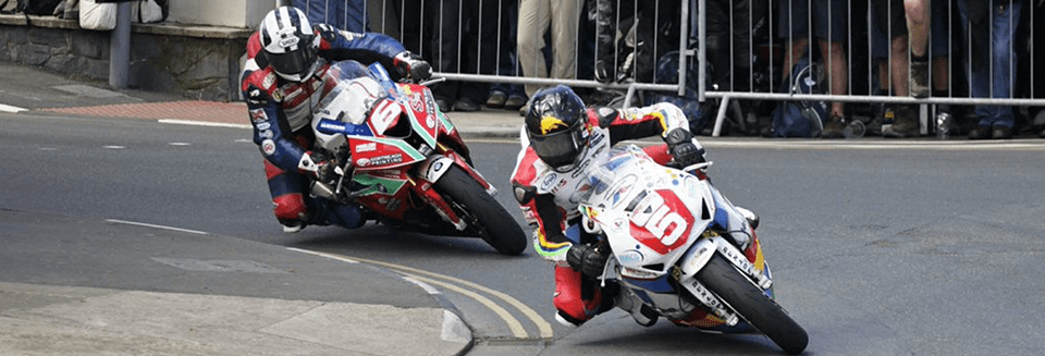 "alt=""Two riders riding at the Isle of Man TT - Isle of Man TT 2019 Travel Packages"""