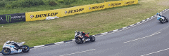 """alt=""""Rider turning the corner at the Isle of Man TT - Representing Isle of Man Road Races 2019 Travel Packages"""""""
