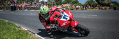 """alt=""""Rider turning at the Isle of Man TT race - Isle of Man TT 2019 Travel Packages"""""""