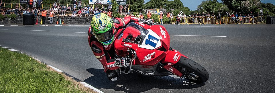 "alt=""Rider turning at the Isle of Man TT race - Isle of Man TT 2019 Travel Packages"""