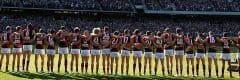 "alt=""Essendon Players Standing Side by Side Each Other at the MCG - 2019 ANZAC Day Clash Travel Packages & Deals"""